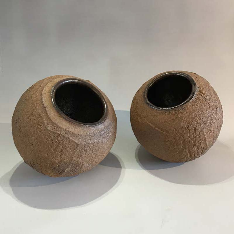 Patricia Shone From left: 27b. and 27a. Earth Jars, Hand formed crank clay, wood-fired with tenmoku glaze interior hts18 cm.